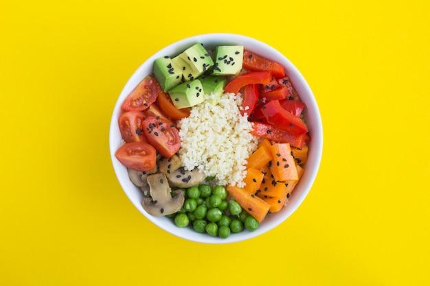 Tigela de puxão vegan com cuscuz e legumes na tigela branca no centro do fundo amarelo. vista do topo. copie o espaço. fechar-se.