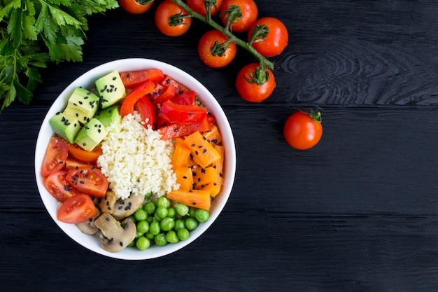 Tigela de puxão vegetariano com cuscuz e legumes na tigela branca sobre o fundo preto de madeira. vista do topo. copie o espaço. fechar-se.