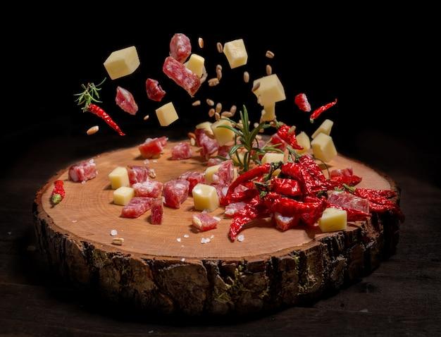 Tigela de queijo e salame em cubos em uma placa de madeira