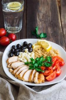 Tigela de quinua de frango saudável com tomate cereja, azeitonas feta e salsa em fundo de madeira