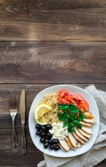 Tigela de quinua de frango saudável com tomate cereja, queijo feta, azeitonas e salsa na superfície de madeira rústica. vista superior com espaço para texto.