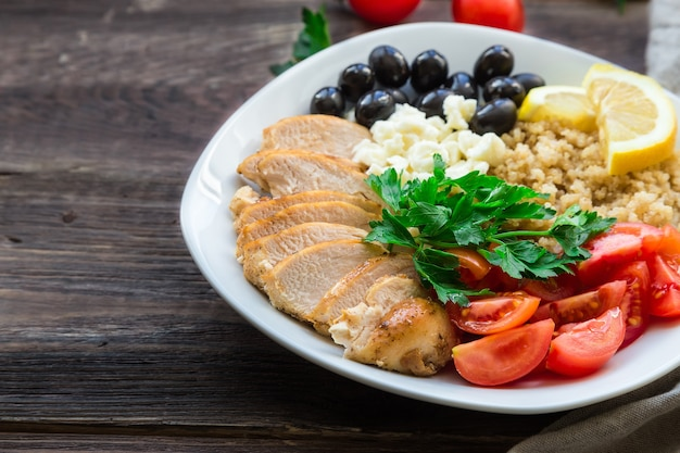 Tigela de quinua de frango saudável com tomate cereja, queijo feta, azeitonas e salsa na superfície de madeira rústica.