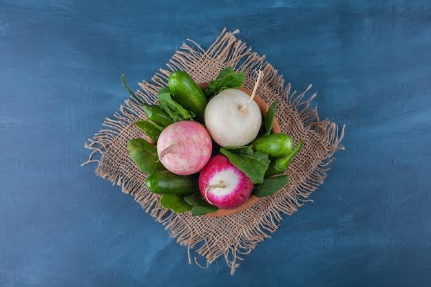 Tigela de rabanetes brancos e vermelhos saudáveis com verdes na superfície azul.