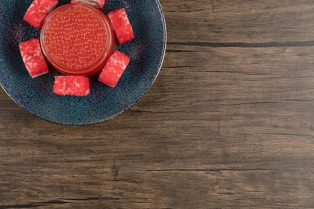 Tigela de rolos de sushi e caviar vermelho na mesa de madeira