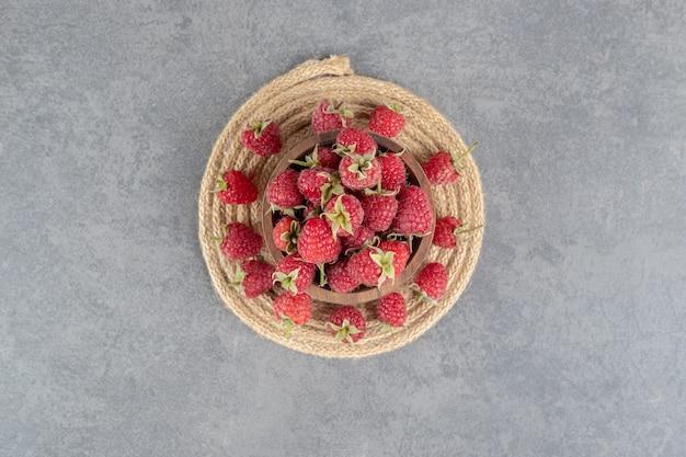 Tigela de saborosas framboesas vermelhas em fundo de mármore. foto de alta qualidade