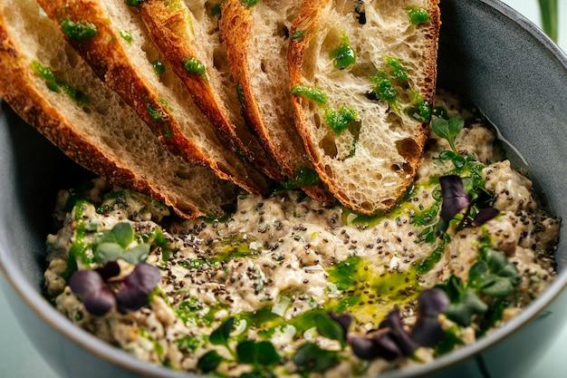 Tigela de saboroso baba ghanoush com pão torrado no fundo azul