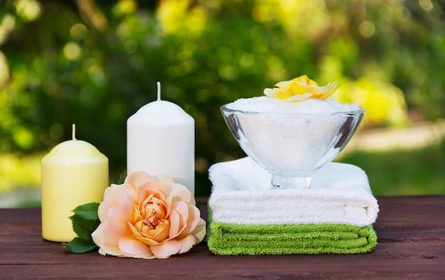 Tigela de sal marinho perfumado, pilha de toalhas macias, velas e rosa perfumada.