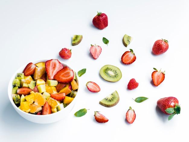 Tigela de salada de fruta saborosa perto de pedaços de morango e kiwi no fundo branco
