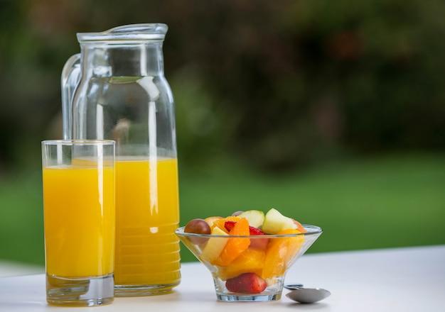 Tigela de salada de frutas com suco de laranja na mesa