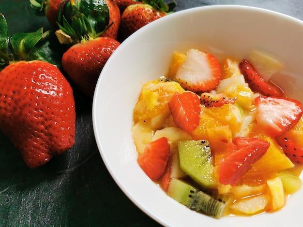 Tigela de salada de frutas frescas cercada por uma variedade de frutas preparadas na hora.