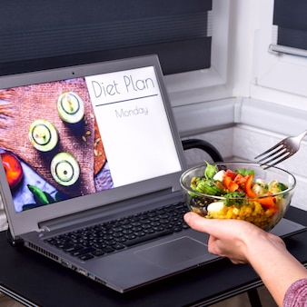 Tigela de salada de legumes nas mãos femininas perto do laptop na área de trabalho