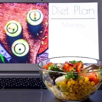 Tigela de salada de legumes perto do laptop na área de trabalho