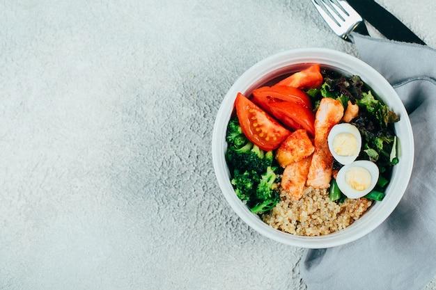 Tigela de salada de peixe com salmão, cuscuz, mistura de salada, feijão verde, brócolis, tomate, ovos de codorna