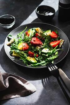 Tigela de salada de verão com rúcula, morango, queijo brie, cominho e mel searved na parede preta com garfo e faca pretos. conceito de alimentação saudável. vista superior com copyspace. fechar-se. luz dura