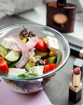 Tigela de salada grega ao lado de perfume de batom e mulher