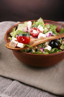 Tigela de salada grega servida no guardanapo na mesa de madeira em fundo escuro