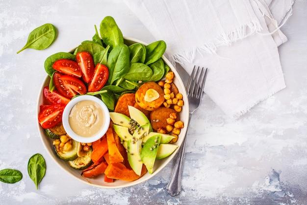 Tigela de salada vegano com legumes cozidos, grão de bico, abacate e molho de tahine em um fundo branco