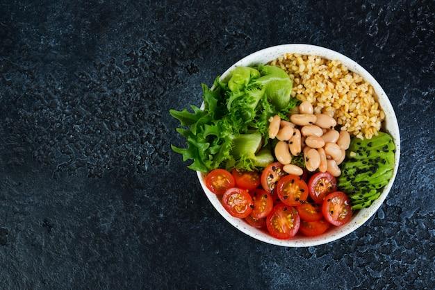 Tigela de salada vegetariana em um fundo preto de concreto em um prato. salada de bulgur e legumes frescos. o conceito de alimentação limpa e alimentação saudável. foto horizontal com espaço de cópia. vista do topo