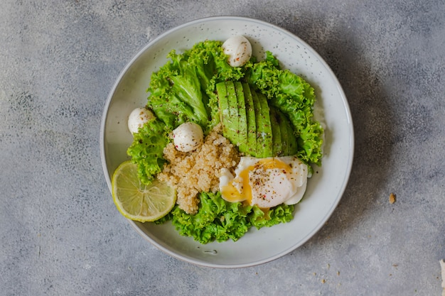 Tigela de salada verde com quinoa, mussarela, abacate, ovo escalfado, alface, limão e azeite na superfície de pedra cinza. conceito de alimentação saudável. fechar-se