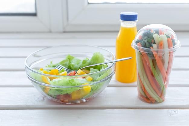 Tigela de salada verde com vegetais crus e garrafa de suco de laranja dieta para perda de peso e nutrição correta