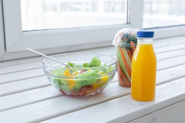 Tigela de salada verde, vegetais crus e uma garrafa de suco de laranja. perda de peso, dieta e certo