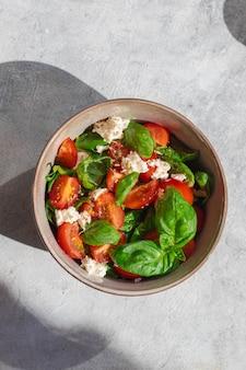 Tigela de salada verde verão com tomate, manjericão e queijo mussarela