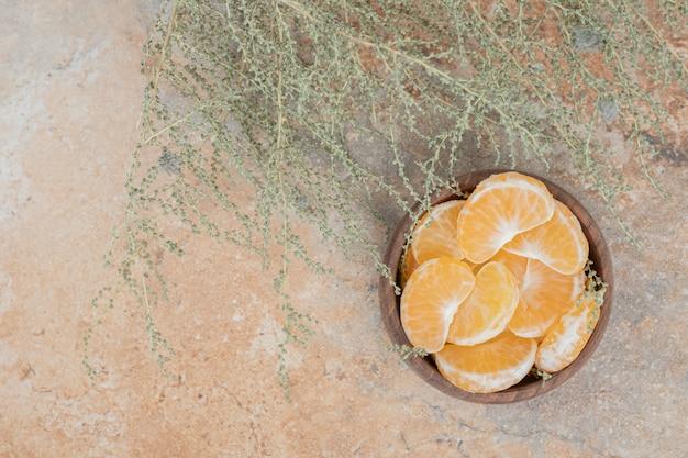 Tigela de segmentos de tangerina fresca em fundo de mármore.
