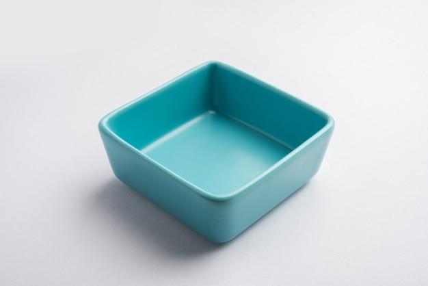 Tigela de servir de cerâmica azul vazia, isolada sobre uma superfície branca ou cinza