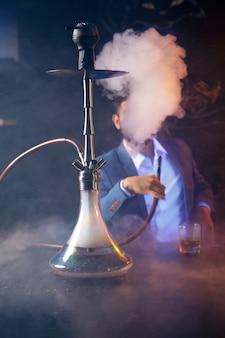 Tigela de shisha de argila com tabaco defeituoso artesanal e bobina de coco encarnado com fundo preto de fumaça de narguilé isolado. fumando narguilé no conceito de festa