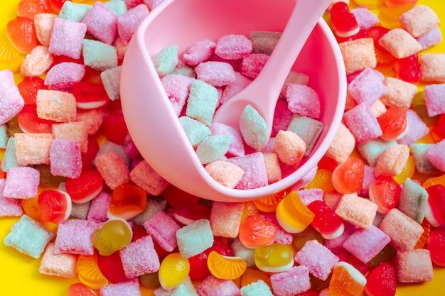 Tigela de silicone para louça infantil com colher. servindo comida para bebê, louça infantil. a tigela e a colher de silicone rosa estão em uma pilha de doces e geleias. foto brilhante e colorida de forma plana