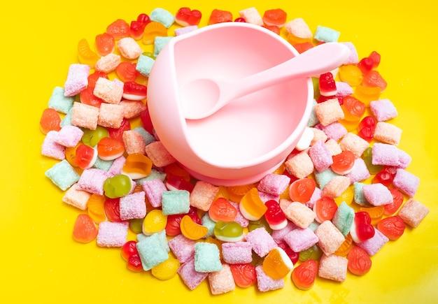 Tigela de silicone para louça infantil com colher. servindo comida para bebê, louça infantil. a tigela e a colher de silicone rosa estão em uma pilha de doces e geleias. foto brilhante e colorida.