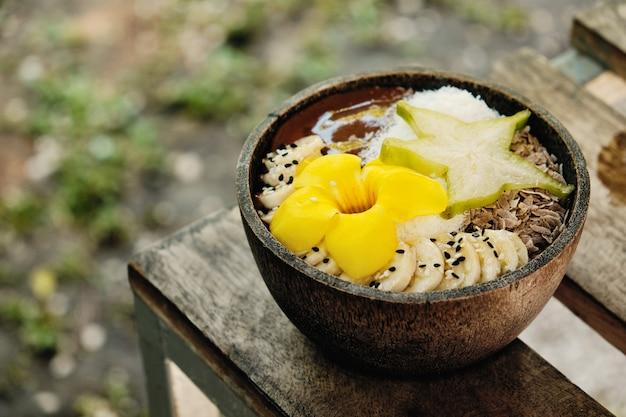Tigela de smoothie com frutas tropicais carambola e bananas decorada com uma flor amarela tropical