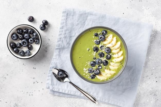 Tigela de smoothie de chá verde matcha com banana, mirtilos, chia, coco. café da manhã vegan