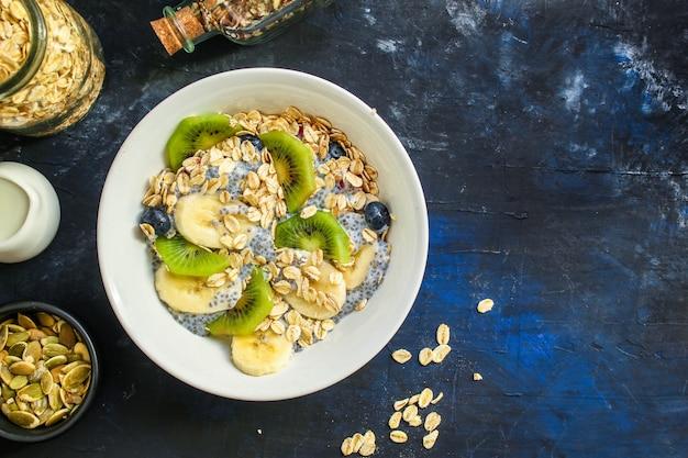 Tigela de smoothie de comida saudável, aveia, sementes de chia no fundo escuro de concreto