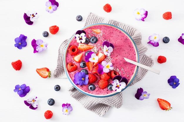 Tigela de smoothie de verão saudável berry com flores e sementes de chia