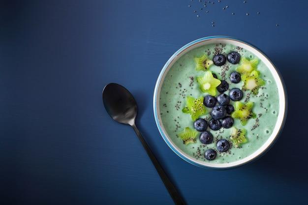 Tigela de smoothie saudável spirulina com mirtilo, estrelas de kiwi e semente de chia