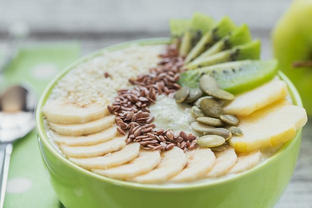 Tigela de smoothie verde coberta com kiwi, banana, maçãs e sementes em fundo branco de madeira rústico para café da manhã de dieta vegetariana vegana saudável. conceito de comida saudável. fechar-se