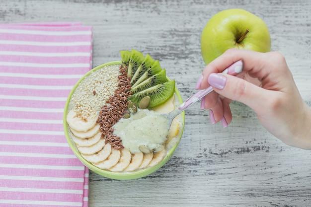 Tigela de smoothie verde coberta com kiwi, banana, maçãs e sementes em fundo branco de madeira rústico para café da manhã de dieta vegetariana vegana saudável. conceito de comida saudável. mão feminina segura uma colher. vista do topo