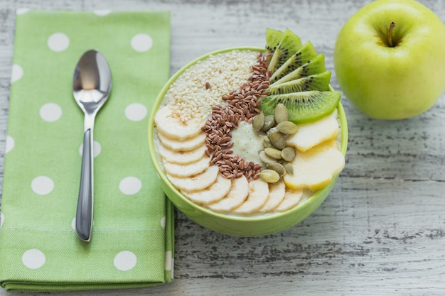 Tigela de smoothie verde coberta com kiwi, banana, maçãs e sementes em fundo branco de madeira rústico para café da manhã de dieta vegetariana vegana saudável. conceito de comida saudável. vista do topo