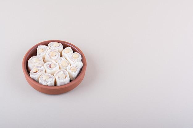 Tigela de sobremesa doce de lokum com nozes em fundo branco. foto de alta qualidade