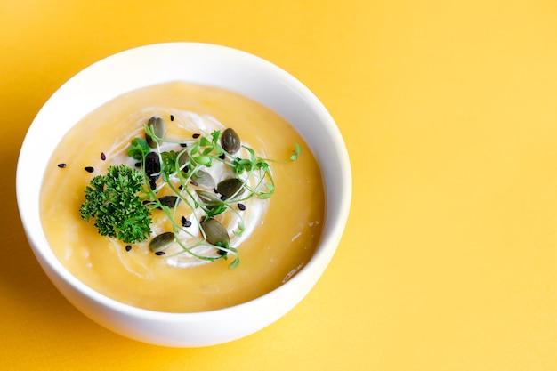 Tigela de sopa de abóbora com folha verde