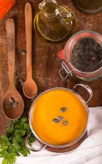 Tigela de sopa de abóbora em fundo de madeira rústico.