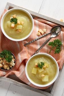 Tigela de sopa de batata-doce cremosa com croutons na bandeja de madeira