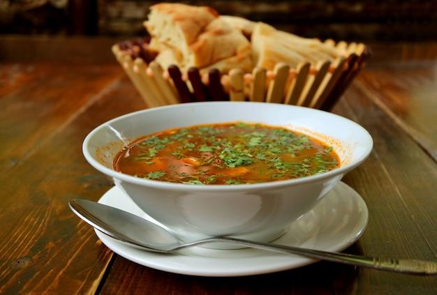 Tigela de sopa de carne georgiana khashi servido com pão shotis puri na mesa de madeira