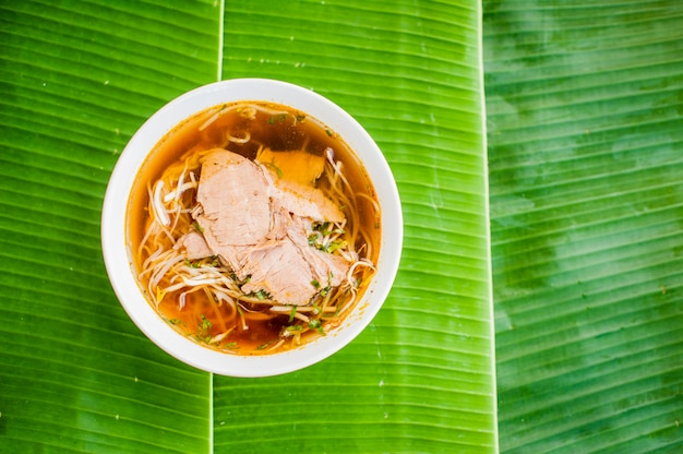 Tigela de sopa de carne vietnamita tradicional pho bo em fundo de folha de banana.