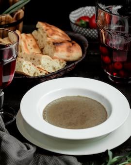 Tigela de sopa de cogumelos servida com pão tandoor