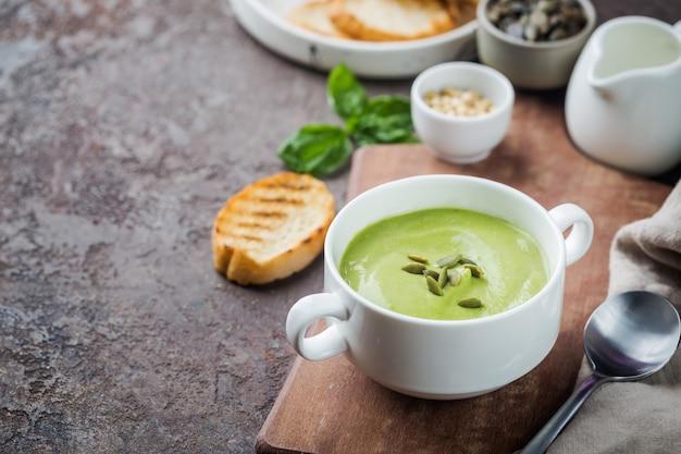 Tigela de sopa de creme de brócolis e ervilhas verdes em uma tigela branca com abacate