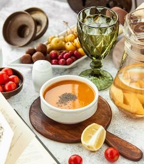Tigela de sopa de lentilha servida na panela de servir de madeira