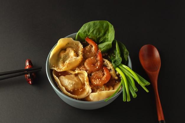 Tigela de sopa de macarrão com camarão, wontons e espinafre