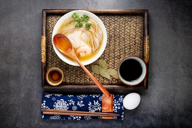 Tigela de sopa de macarrão em uma mesa de madeira
